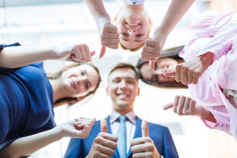 Succesvolle bedrijfsmensen met duimen omhoog en glimlachend stock fotografie