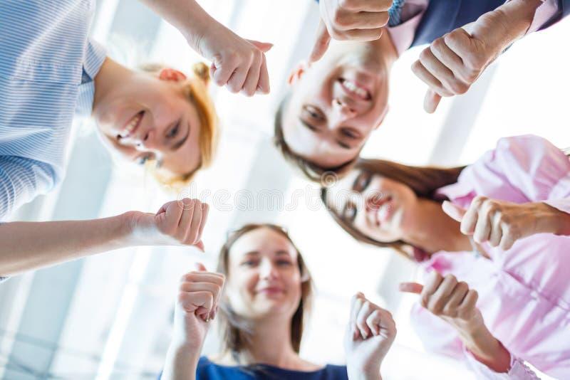 Succesvolle bedrijfsmensen met duimen omhoog en glimlachend royalty-vrije stock afbeelding