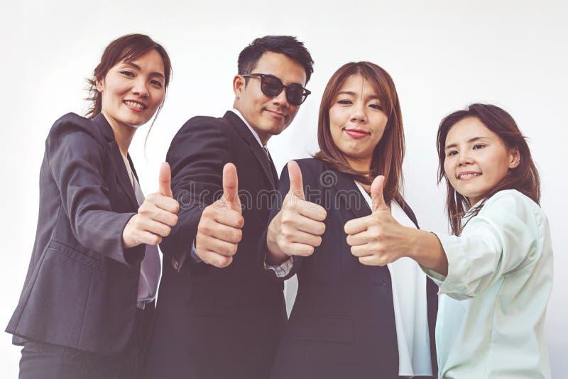 Succesvolle bedrijfsmensen met duimen omhoog en glimlachend, commercieel team stock afbeeldingen