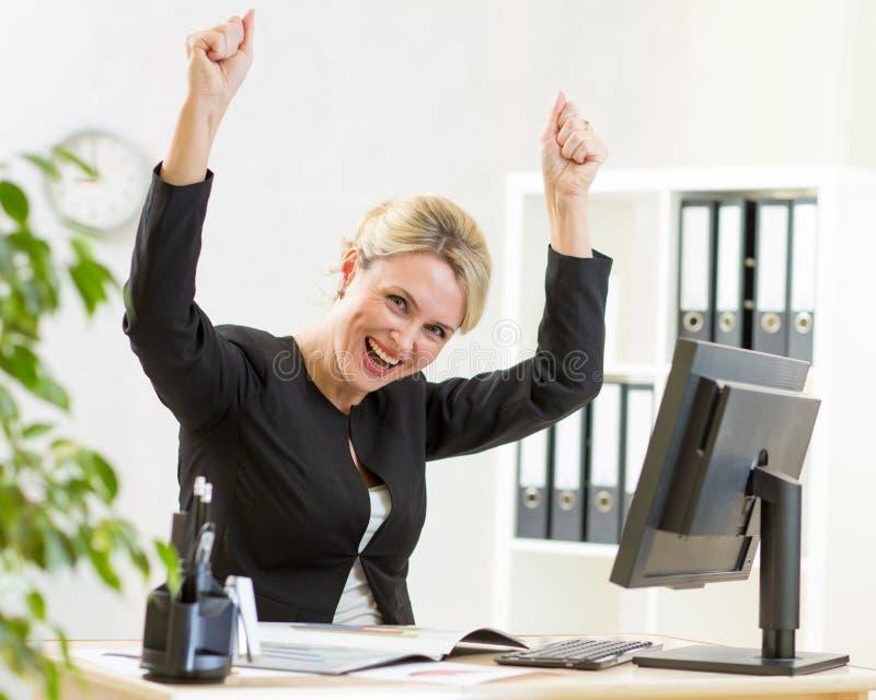 Succesvolle bedrijfsvrouw met wapens omhoog in bureau royalty-vrije stock foto