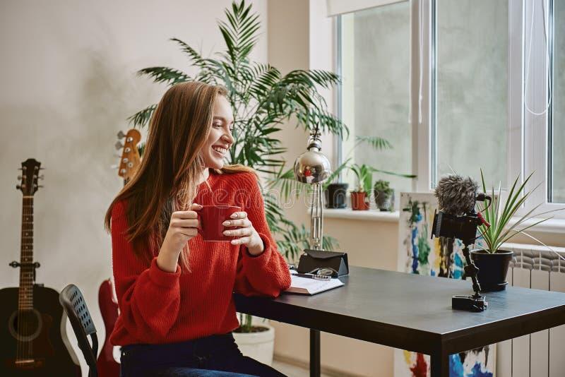 Succesvolle blogger Zijaanzicht van glimlachend wijfje die blogger een thee drinken terwijl thuis het maken van een nieuwe video royalty-vrije stock afbeeldingen