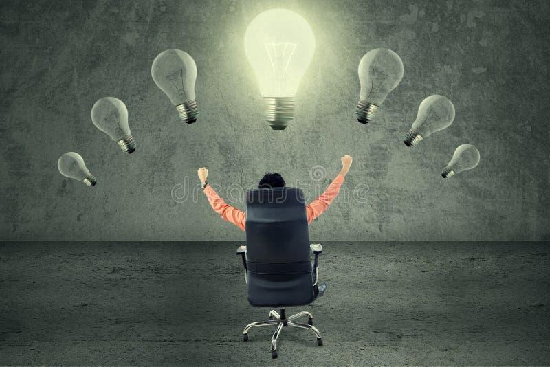 Succesvolle businessperson onder heldere lightbulb royalty-vrije stock afbeeldingen