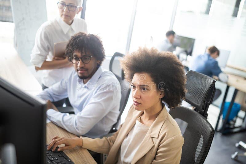Succesvolle commerci?le groep mensen aan het werk in bureau stock afbeeldingen