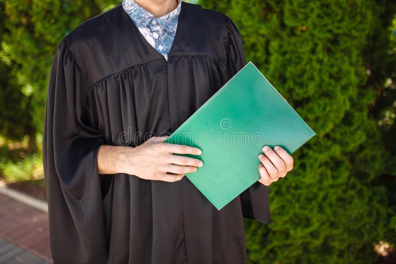 Succesvolle gediplomeerde kerel, in academische kleding, op graduatieposi royalty-vrije stock foto's