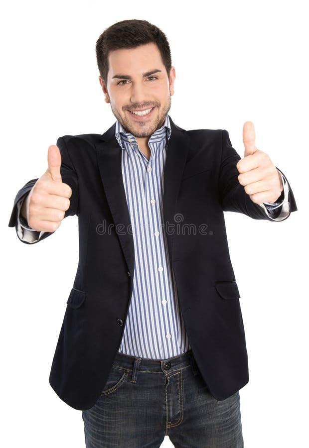 Succesvolle gelukkige geïsoleerde jonge zakenman met omhoog duimen stock foto