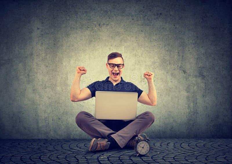 Succesvolle gelukkige mens met vuisten die omhoog op laptop letten stock fotografie