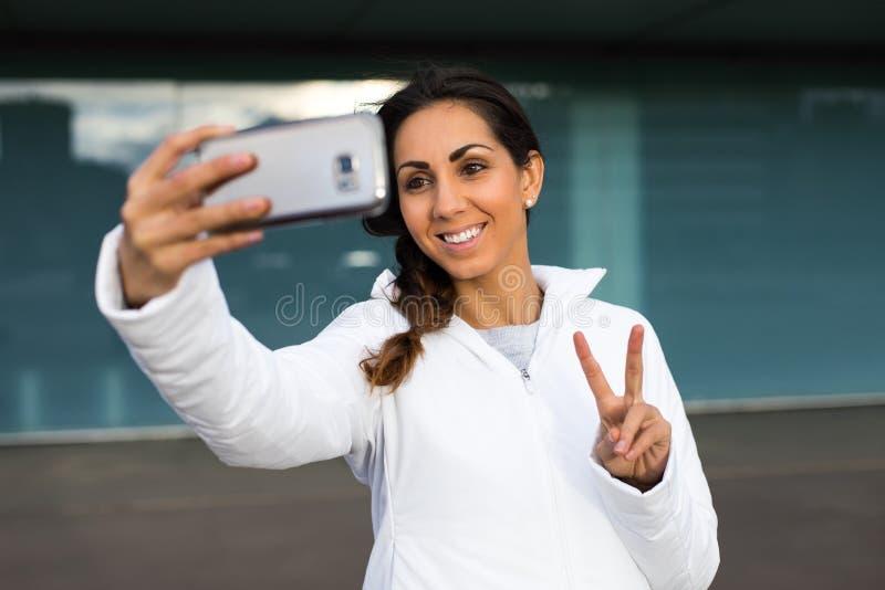 Succesvolle geschiktheidsvrouw die selfie met celtelefoon nemen royalty-vrije stock afbeeldingen
