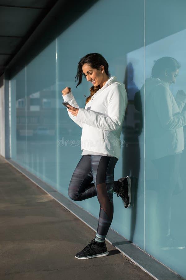 Succesvolle geschiktheidsvrouw die smartphone gebruiken royalty-vrije stock fotografie