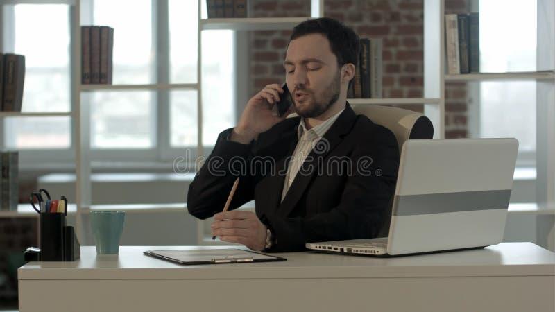Succesvolle jonge bedrijfsmens die op celtelefoon op modern kantoor spreken royalty-vrije stock afbeeldingen