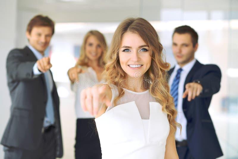 Succesvolle jonge bedrijfsmensen die door vingers in camera richten royalty-vrije stock afbeeldingen