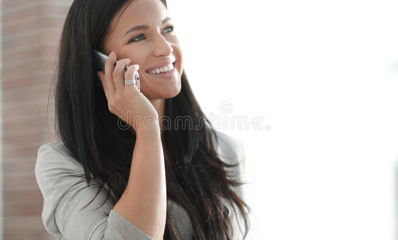 Succesvolle jonge bedrijfsvrouw die op een smartphone spreken stock afbeelding
