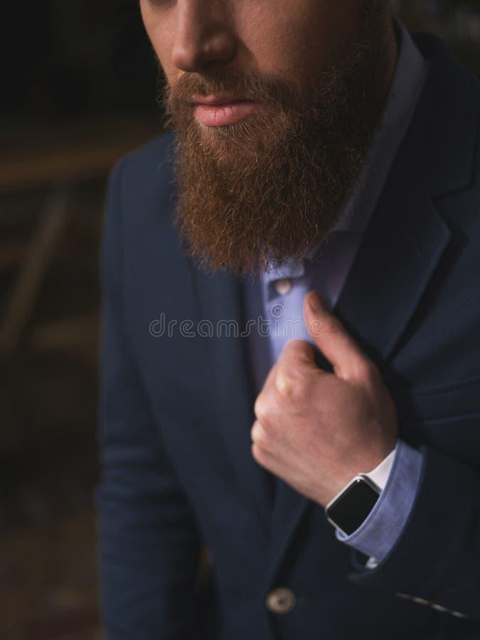 Succesvolle jonge gebaarde zakenman in een kostuum royalty-vrije stock afbeeldingen