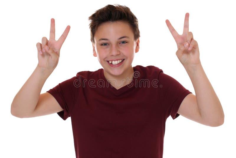 Succesvolle jonge tienerjongen die het overwinningsteken maken stock afbeeldingen