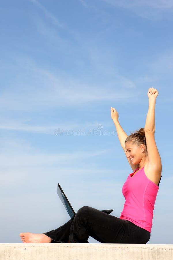Succesvolle jonge vrouw met haar laptop stock foto