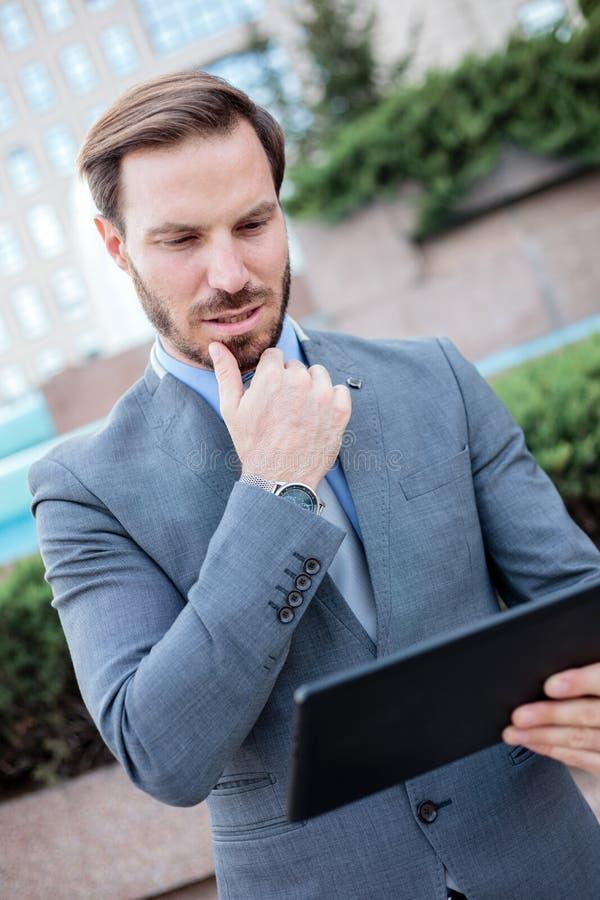 Succesvolle jonge zakenman die aan een tablet voor een bureaugebouw werken Holdingshand op kin royalty-vrije stock foto's