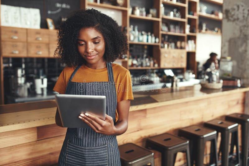 Succesvolle kleine bedrijfseigenaar die digitale tablet in haar koffie gebruiken royalty-vrije stock foto