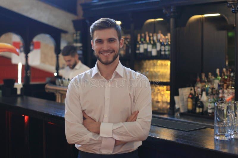 Succesvolle kleine bedrijfseigenaar die zich met gekruiste wapens met werknemer die op achtergrond bevindt koffie voorbereidt stock foto