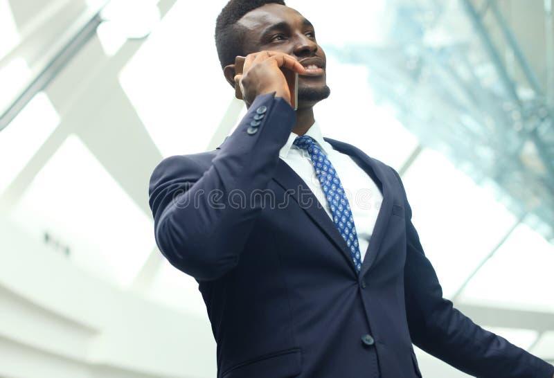 Succesvolle knappe Afrikaanse Amerikaanse zakenman die op mobiele telefoon in modern bureau spreken stock foto