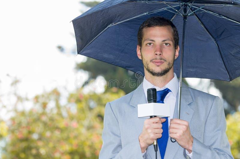 Succesvolle knappe mannelijke journalist die licht dragen stock fotografie
