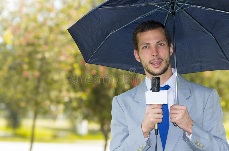 Succesvolle knappe mannelijke journalist die licht dragen stock foto