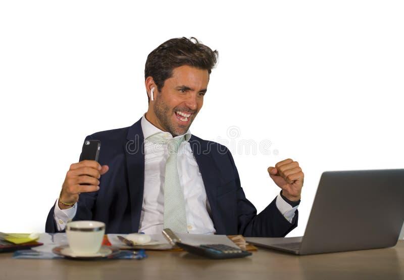 Succesvolle knappe zakenman in kostuum die bij het bureau werken die van de bureaucomputer financieel succes winnend geld vieren  stock fotografie