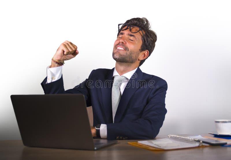 Succesvolle knappe zakenman in kostuum die bij het bureau werken die van de bureaucomputer financieel succes winnend geld vieren  stock afbeelding