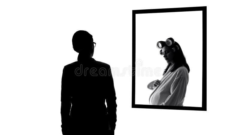 Succesvolle maar eenzame bedrijfsvrouw die zwanger wensen te zijn, spiegelbezinning stock foto's