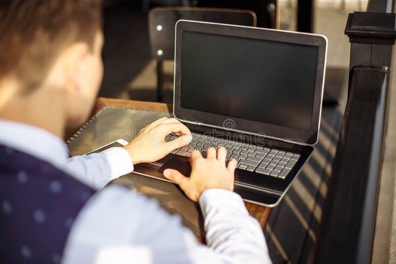 Succesvolle manager die in koffie tijdens onderbreking werken en informatie in Internet over zijn notitieboekjecomputer zoeken royalty-vrije stock foto