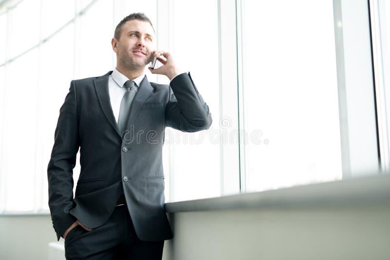 Succesvolle mannelijke ondernemer die op telefoon spreken stock afbeeldingen