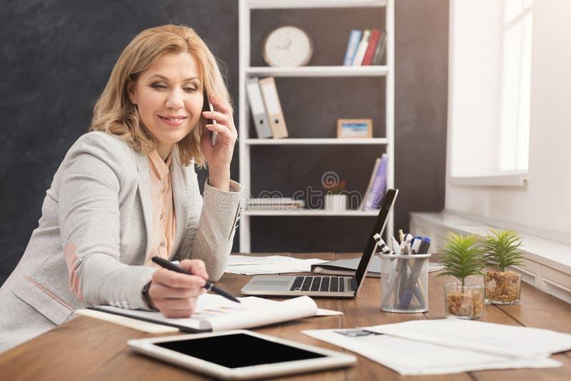 Succesvolle onderneemster aan het werk die op telefoon spreken stock afbeeldingen