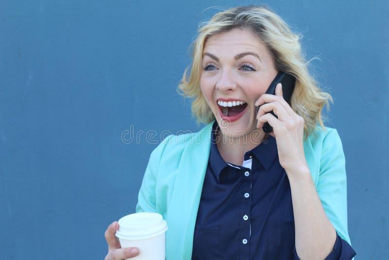 Succesvolle onderneemster die zich voor haar bureau bevinden, die op telefoon spreken die goed nieuws horen Zij is zeer gelukkig stock afbeeldingen