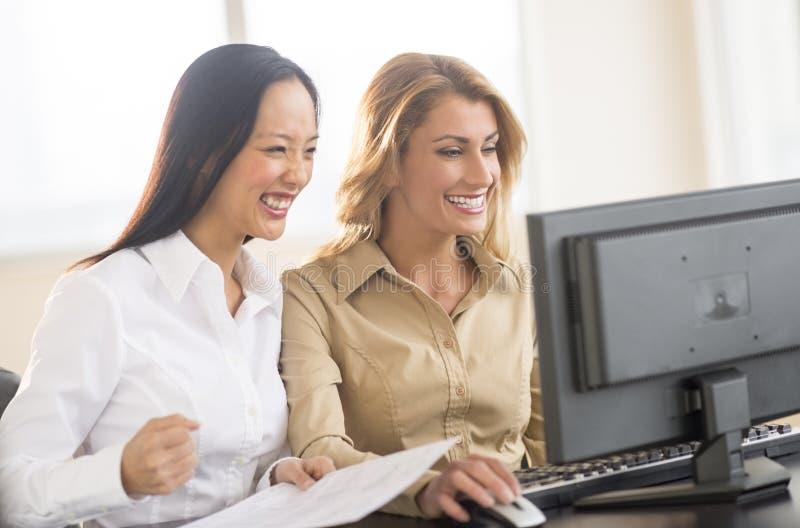 Succesvolle Onderneemsters die Computer in Bureau met behulp van royalty-vrije stock foto