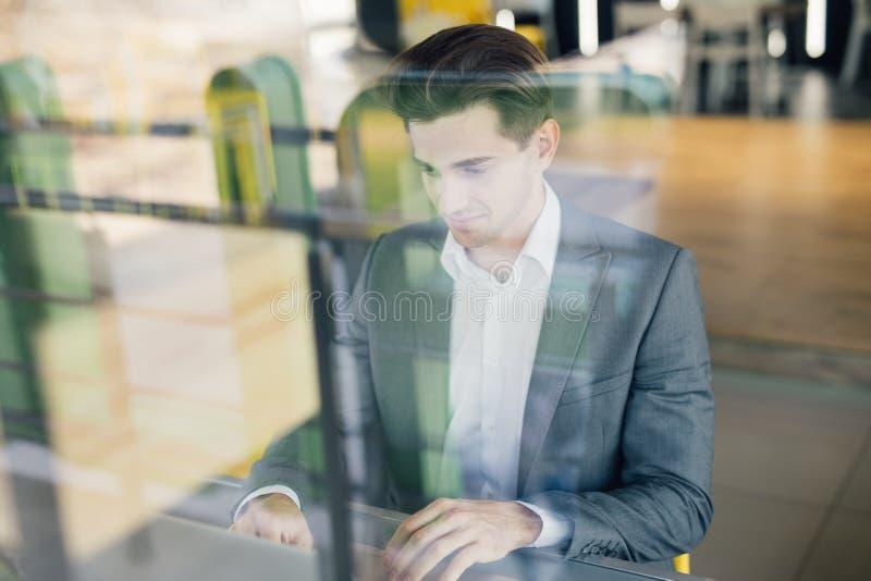 Succesvolle ondernemer die in tevredenheid glimlachen aangezien hij informatie over zijn laptop computer terwijl het werken in ee royalty-vrije stock foto