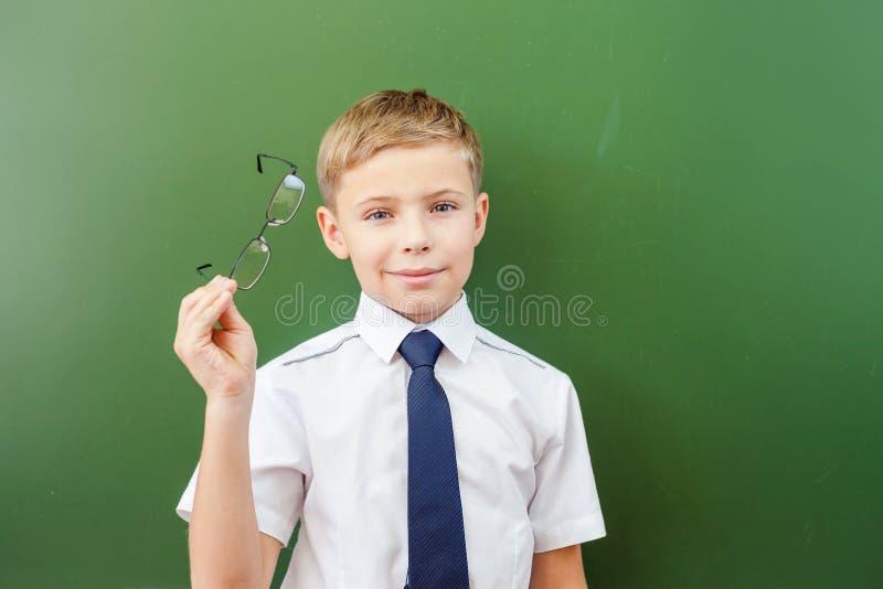 Succesvolle schooljongen die zich dichtbij het bord in schoolklaslokaal bevinden stock afbeelding