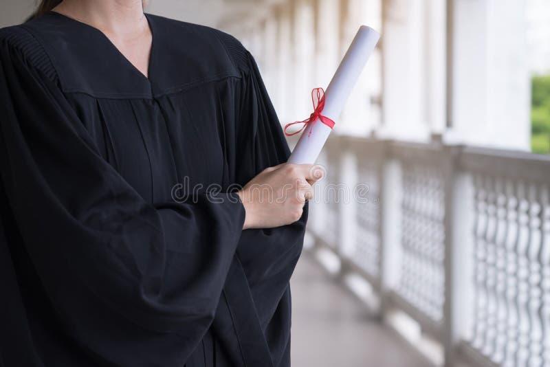 Succesvolle student op hun graduatiedag, gediplomeerd holdingsdiploma, Onderwijs, Graduatie en mensenconcept stock afbeeldingen
