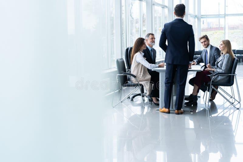 Succesvolle teamleider en bedrijfseigenaar die informele binnenshuis commerci?le vergadering leiden royalty-vrije stock afbeeldingen