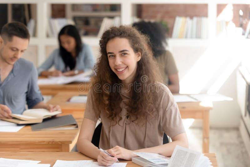 Succesvolle universitaire studentenzitting bij bureau die camera bekijken stock foto's