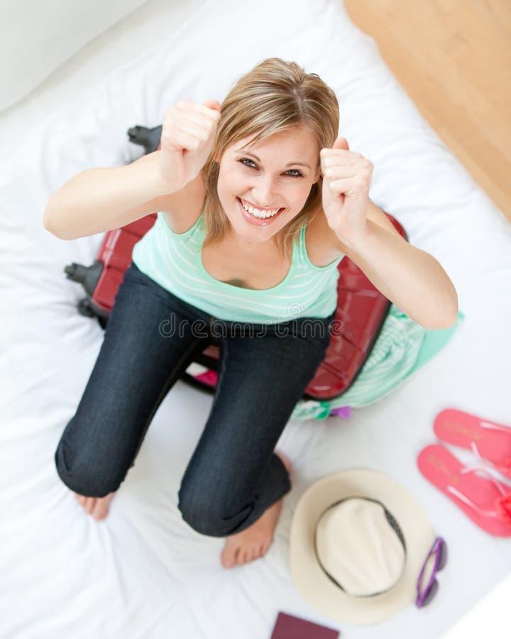 Succesvolle vrouw die haar koffer probeert te sluiten stock foto's