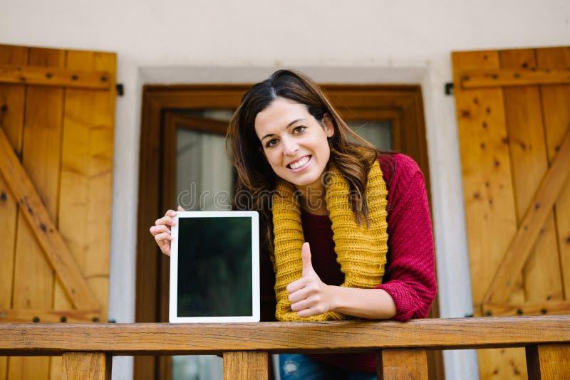 Succesvolle vrouw die het digitale tabletscherm op de herfst tonen stock foto