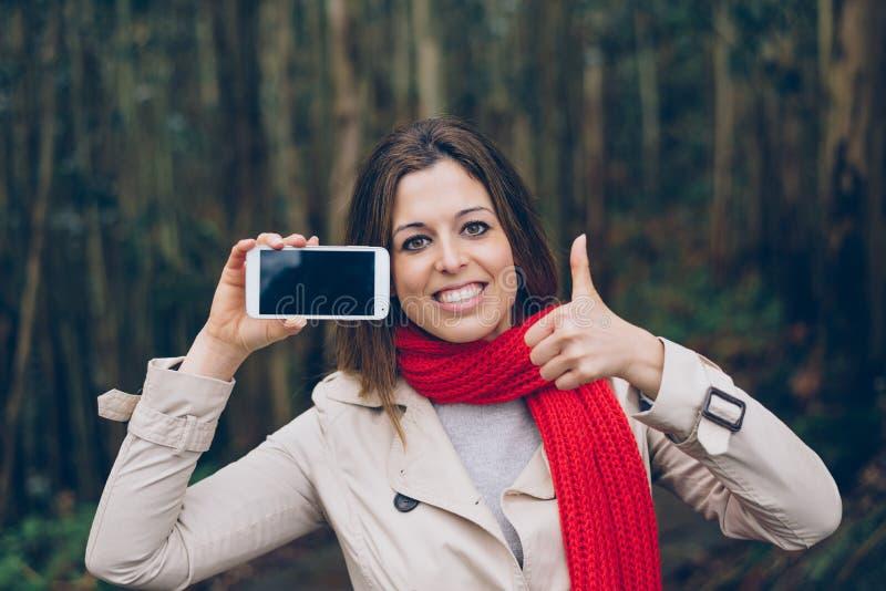 Succesvolle vrouw die het smartphonescherm tonen royalty-vrije stock foto's
