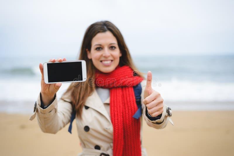 Succesvolle vrouw die smartphone het lege scherm tonen royalty-vrije stock afbeelding