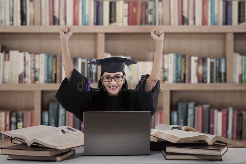 Succesvolle vrouwelijke gediplomeerde met laptop bij bibliotheek royalty-vrije stock fotografie