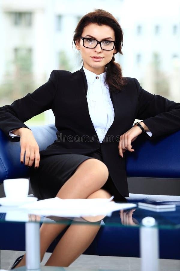 Succesvolle vrouwelijke zitting in bureau stock foto