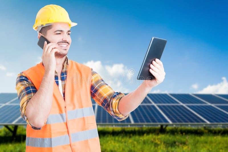 Succesvolle werkman op cellphone en tablet ter beschikking stock afbeeldingen