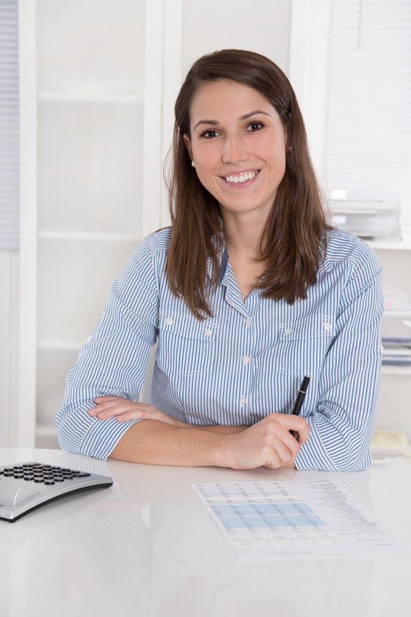 Succesvolle zaken: vrouw die in blauwe blousezitting bij des glimlachen stock afbeeldingen