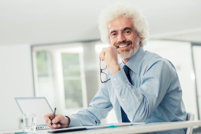Succesvolle zakenman die bij bureau werken stock afbeelding