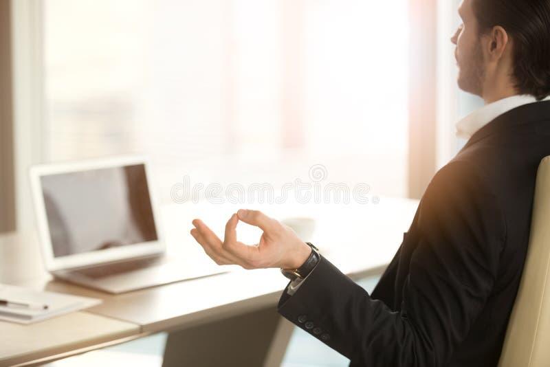 Succesvolle zakenman die bij het werkbureau mediteren in modern bureau royalty-vrije stock foto's
