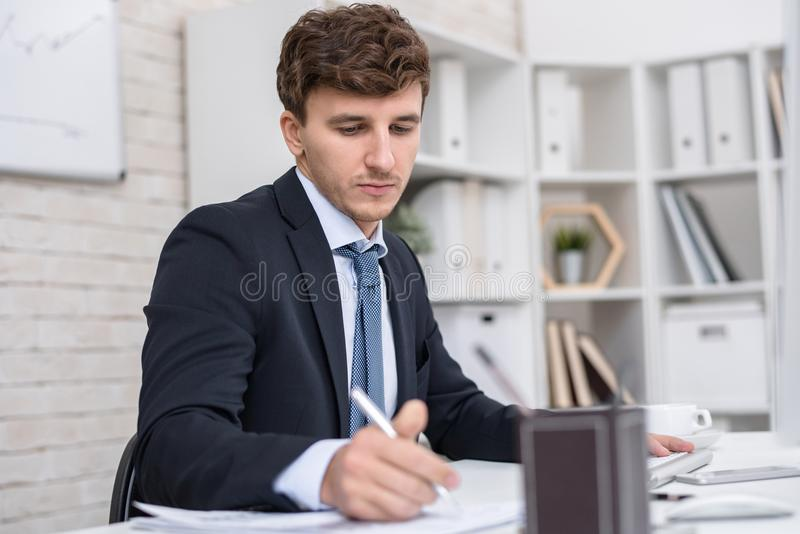Succesvolle zakenman die in bureau werken stock fotografie