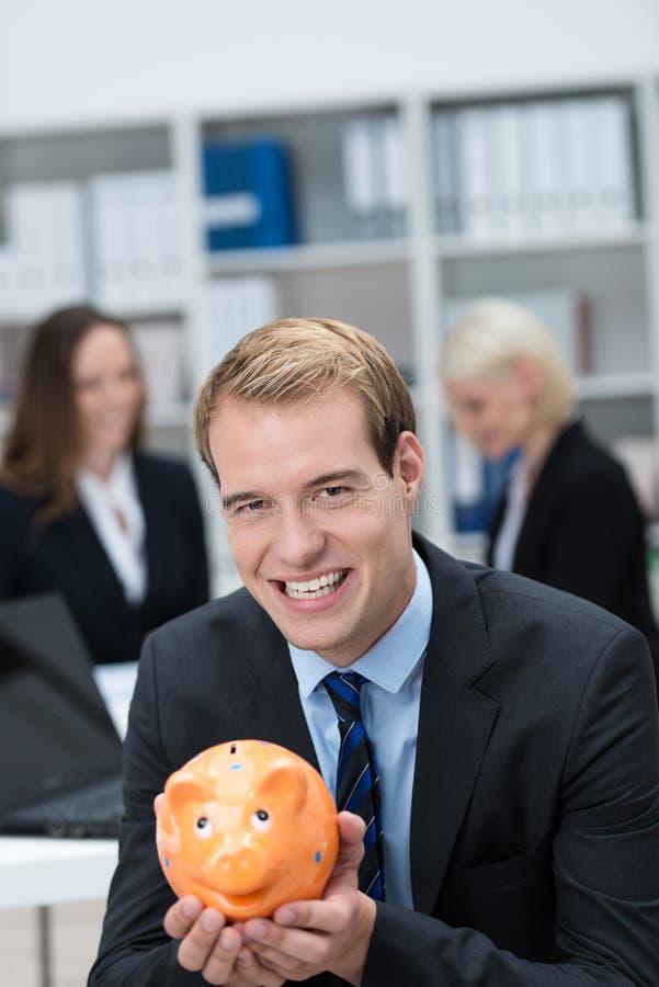 Succesvolle zakenman die een spaarvarken houden stock afbeelding