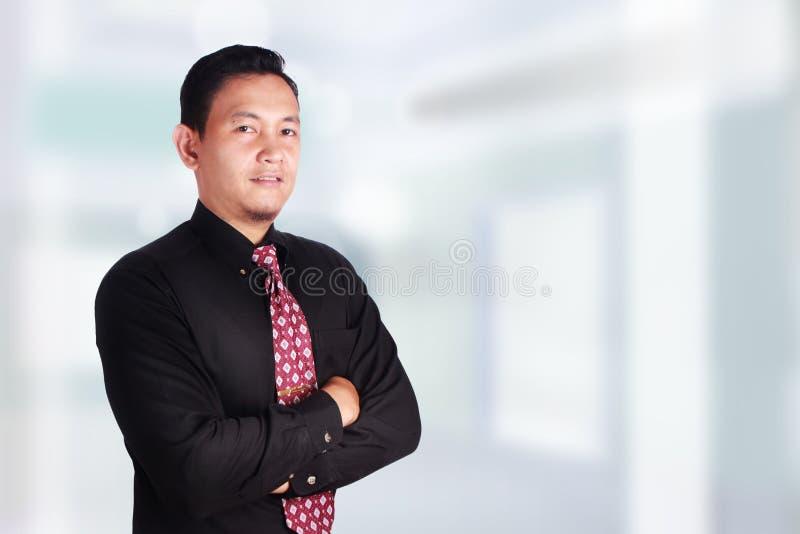 Succesvolle zakenman die, gekruiste wapens glimlachen stock foto